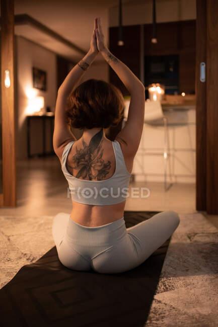 Анонимная женщина, сжимающая руки над головой и медитирующая в позе Лотоса ночью — стоковое фото