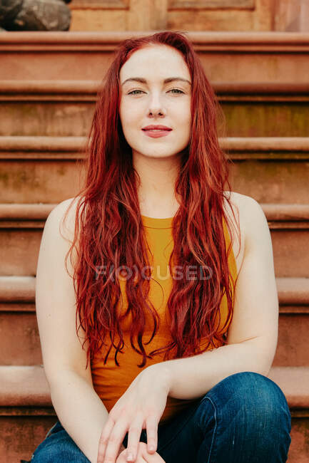 Portrait of a young woman with red hair sitting outdoors on a stoop — Stock Photo