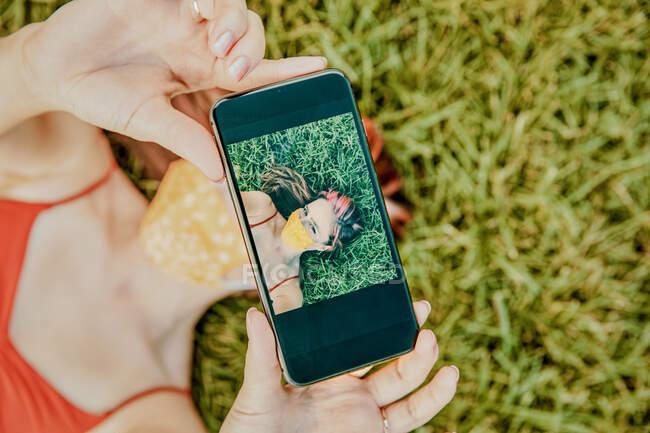 Jovem mulher na grama tomando selfie usando máscara facial — Fotografia de Stock