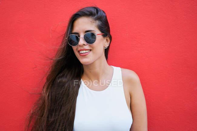 Молода жінка з довгим волоссям в стильних сонцезахисних окулярах і стоїть біля червоної стіни будинку в місті. — стокове фото