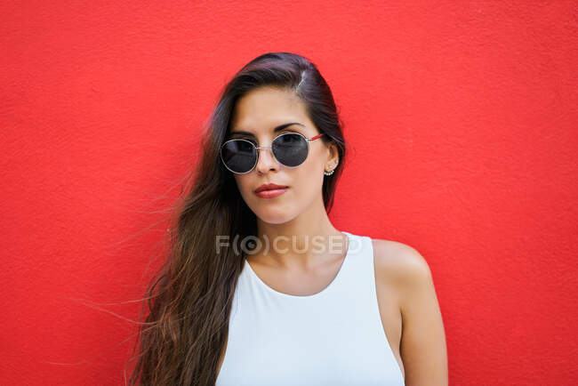 Young woman with long hair wearing stylish sunglasses and standing near red building wall in city — Stock Photo