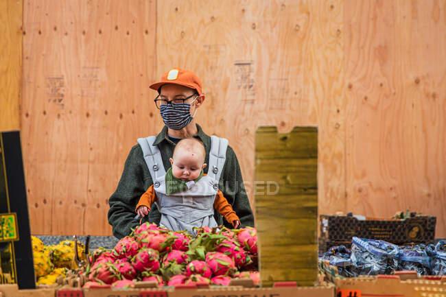 Отец с милой девочкой покупает питайи в городе во время пандемии коронавируса — стоковое фото