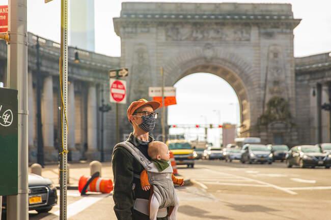 Homem usando máscara facial carregando filha em carrinho de bebê enquanto estava na rua na cidade durante COVID-19 — Fotografia de Stock