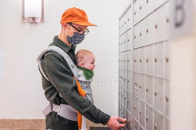 Pai vestindo máscara facial abrindo armário no quarto enquanto carrega bebê menina durante a crise COVID-19 — Fotografia de Stock