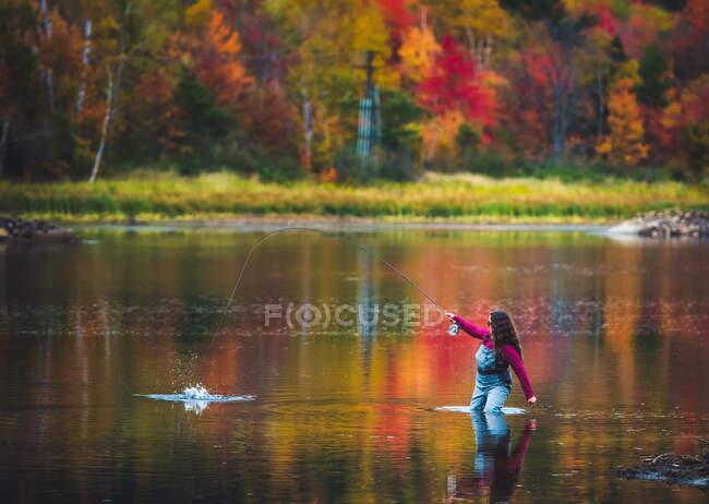 Жіночий англер ловить рибу під час осіннього листяного сезону. — стокове фото