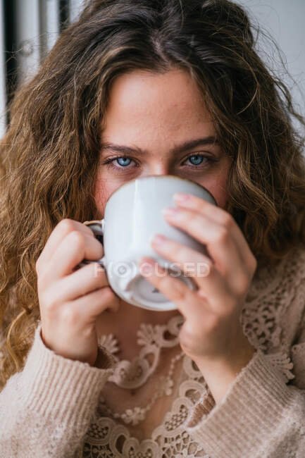 Young female with blue eyes sipping hot drink and looking at camera — Stock Photo