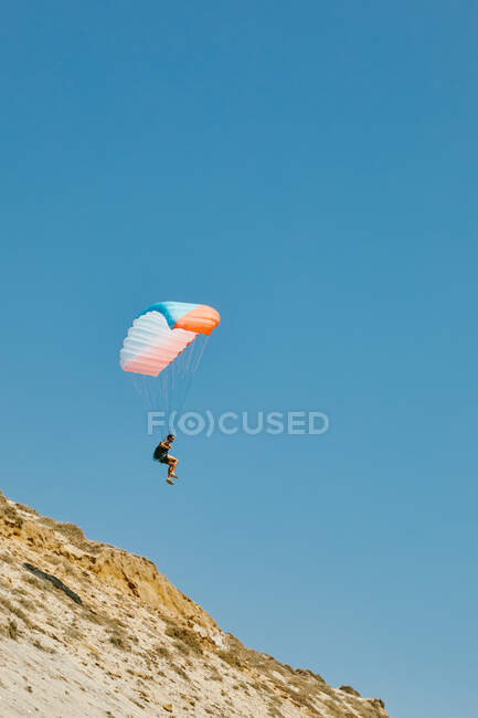 Jeune homme parapente pendant l'été au large des falaises à Baja, Mexique — Photo de stock