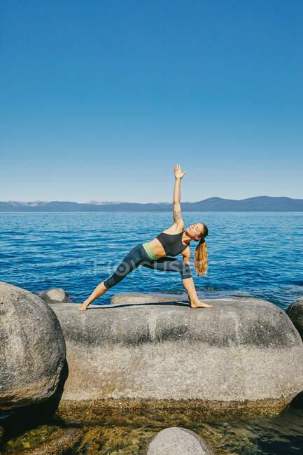 Молодая женщина практикует йогу у моря — стоковое фото