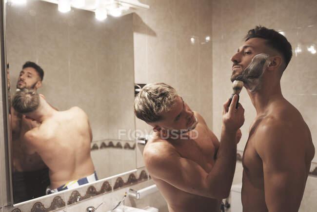 Um menino ajuda seu melhor amigo a se barbear — Fotografia de Stock
