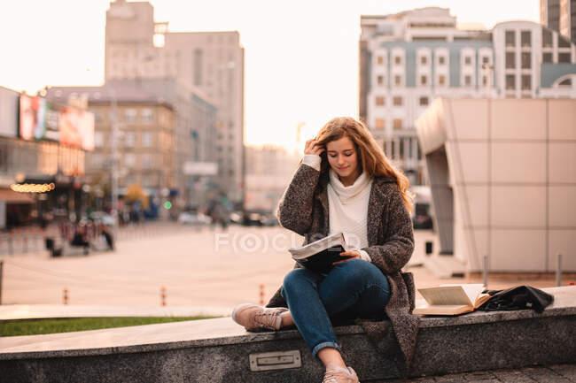 Heureuse adolescente étudiante étudiant tout en étant assise sur le campus en automne — Photo de stock