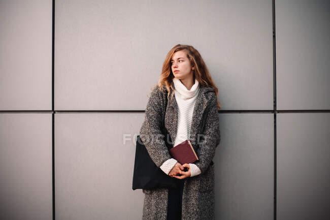 Retrato de estudante feminina pensativo segurando livro de pé contra a parede cinza — Fotografia de Stock