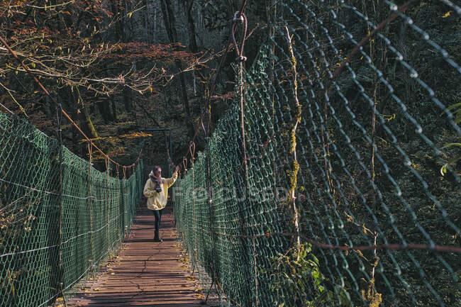 Mujer joven con cámara cruzando puente colgante - foto de stock