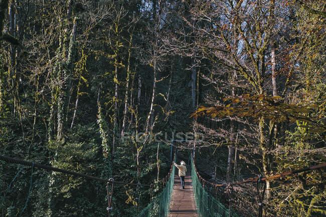 Mujer joven tomando foto puente colgante - foto de stock