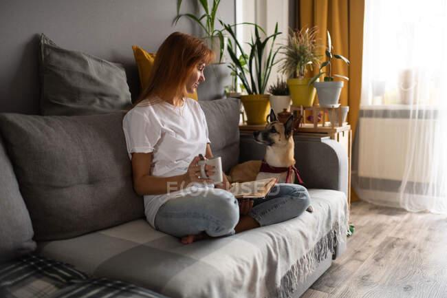 Жінка середнього віку з кухлем гарячого напою читає книжку і дивиться на собаку, сидячи схрещеною на дивані. — стокове фото