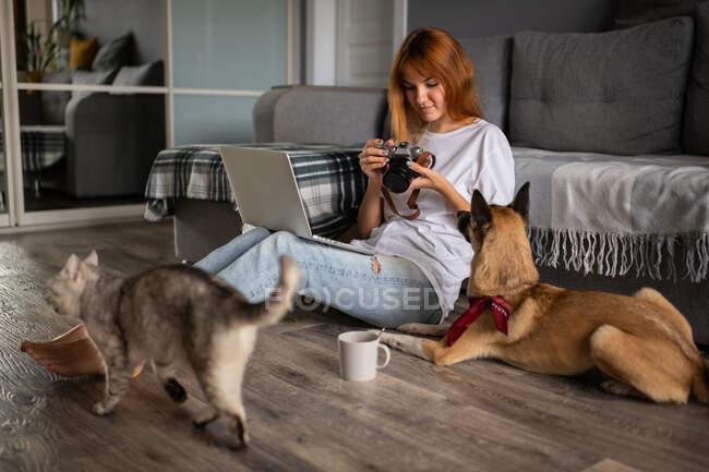Жінка з ноутбуком на фотоапараті, сидячи на підлозі біля собаки й кота вдома. — стокове фото