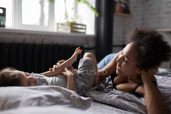 Happy mixed race girl and woman smiling and looking at each other while lying on soft bed after awakening in morning at home — Stock Photo