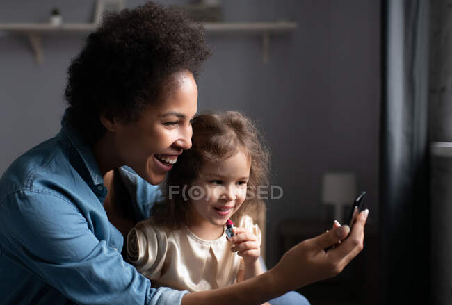 Delighted ethnic mother smiling and showing pocket mirror to mixed race girl with lipstick while teaching daughter to apply makeup at home — Stock Photo