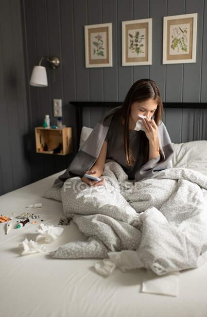 Mujer joven enferma con teléfono inteligente soplando la nariz en el tejido mientras está sentado en la cama blanda en casa - foto de stock