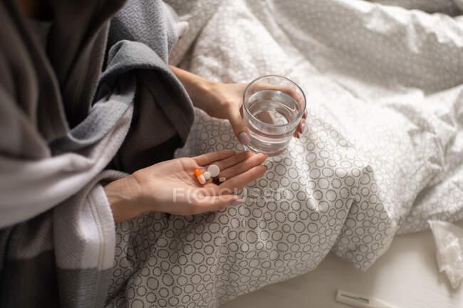 De arriba mujer enferma anónima con un vaso de agua y un puñado de medicamentos para la gripe sentados debajo de una manta caliente en la cama en casa - foto de stock