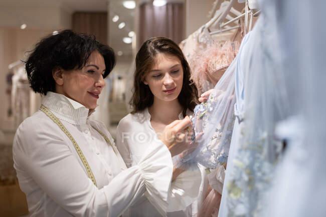 Elegante adulto proprietario atelier femminile con nastro di misura sul collo aiutare la giovane donna nella scelta di abito da ballo e mostrando delicato vestito blu — Foto stock