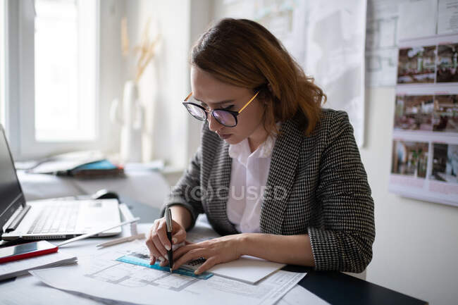 Young woman in glasses and formal wear using pen and ruler to draw blueprint while sitting at table in contemporary office — Stock Photo
