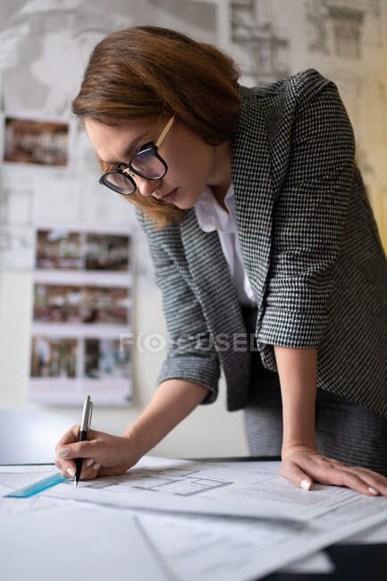 Young businesswoman in glasses making marks on architecture draft and thinking while leaning on table in creative workspace — Stock Photo
