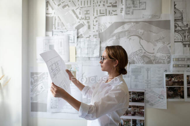 Side view of young businesswoman in glasses reading blueprint while working on interior design project in modern workspace — Stock Photo