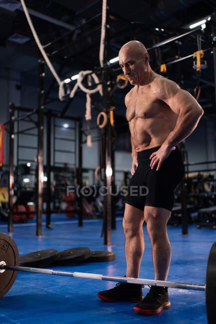 Повна довжина впевнена, що літні спортсмени з руками на талії стоять біля барила і відпочивають під час занять спортом перед важкими вправами в спортзалі — стокове фото