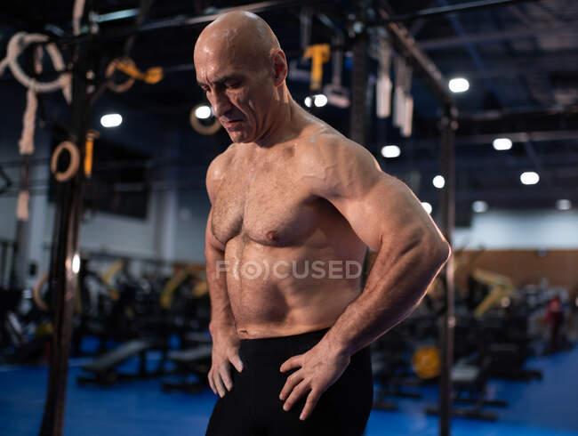 Fuerte atleta senior con las manos en la cintura haciendo una pausa en el entrenamiento funcional intenso en el gimnasio moderno - foto de stock