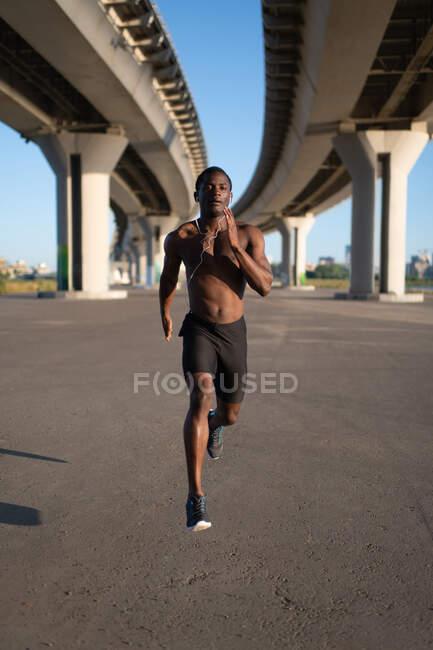 Ajuste jovem velocista com tronco nu correndo em pista vazia sob ponte na manhã ensolarada — Fotografia de Stock