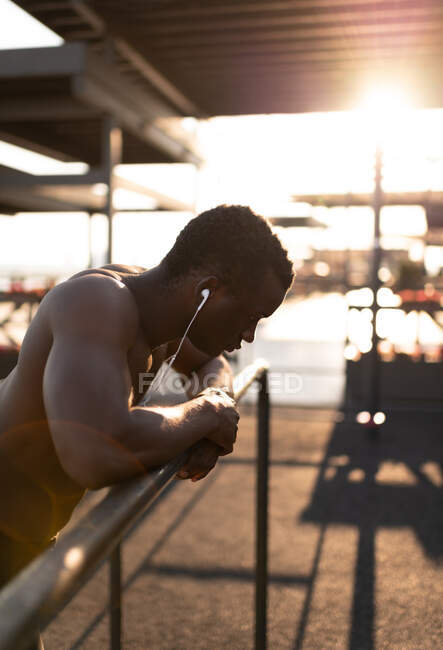 Rétroéclairé fatigué sportif afro-américain jeune homme avec torse nu appuyé sur la main courante avec les deux mains et se reposant tout en écoutant de la musique avec des écouteurs pendant l'entraînement — Photo de stock