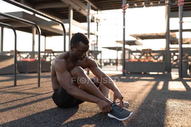 Athletic African American man sitting and tying shoelaces on sneaker for training in bright sunlight on playground — Stock Photo