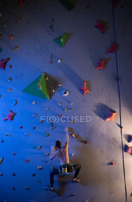 Vue arrière d'un homme torse nu méconnaissable saisissant des poignées et escaladant un mur élevé pendant l'entraînement professionnel de bloc — Photo de stock