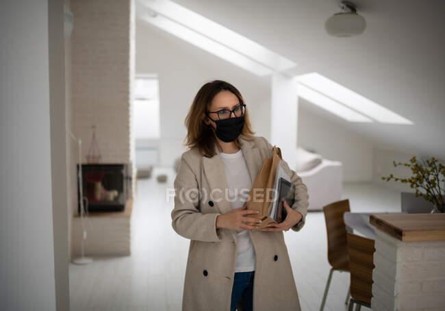 Mujer moderna en ropa casual y máscara protectora que sostiene documentos y bolsa de papel con productos mientras llega a casa después del trabajo y compra durante el brote de coronavirus - foto de stock