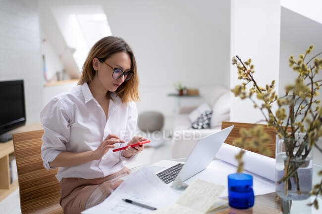Serious young businesswoman in formal outfit and glasses checking message on smartphone while working with laptop and papers in modern apartment — Stock Photo
