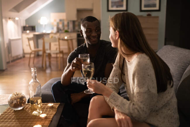 Optimistic African American guy smiling and proposing toast to girlfriend while sitting on couch and drinking wine during romantic date at home — Stock Photo