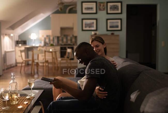 Sorridente giovane donna che abbraccia ridendo uomo afroamericano con telecomando mentre guarda la TV durante appuntamento romantico a casa — Foto stock