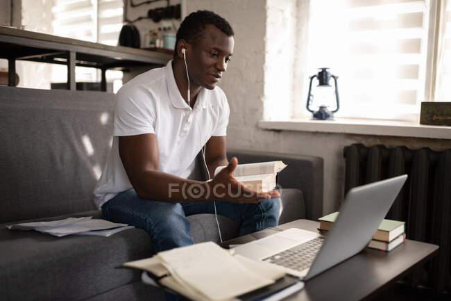 Uomo nero in abiti casual e auricolari seduti sul divano e discutere libro con tutor durante la lezione remota a casa — Foto stock