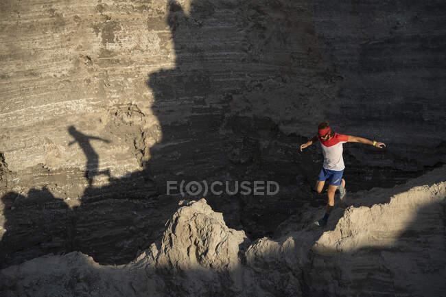 Un rastro de hombre corriendo por terreno técnico dejando polvo en su camino - foto de stock