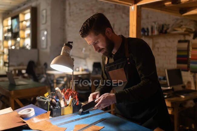 Bearded male artisan preparing tools over illuminated table while working with leather in home studio — Stock Photo
