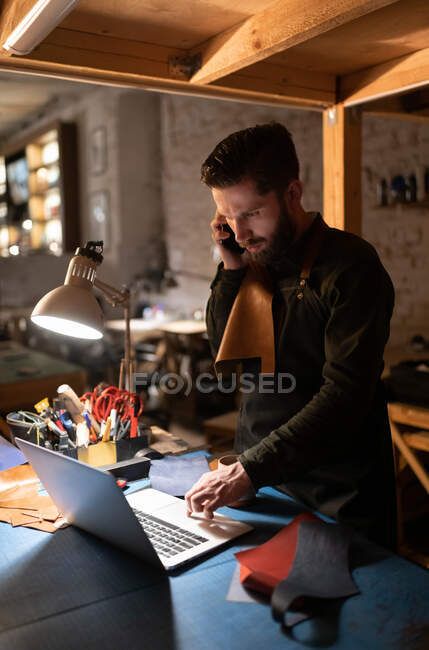Bearded male artisan talking with client from another country and using laptop to sell leather handicraft near lamp in professional studio — Stock Photo