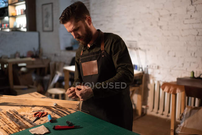 Bearded male artisan in apron frowning and pondering over leather handicraft while working in professional home studio — Stock Photo
