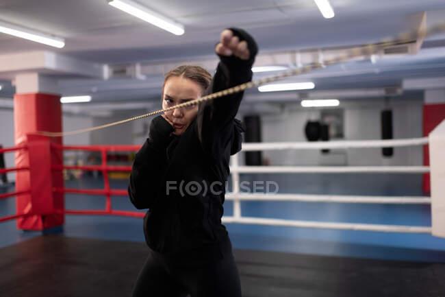 Вирішальна жінка в чорному спортивному манежі робить удар джебом, практикуючи тіньовий бокс на рингу в спортзалі — стокове фото