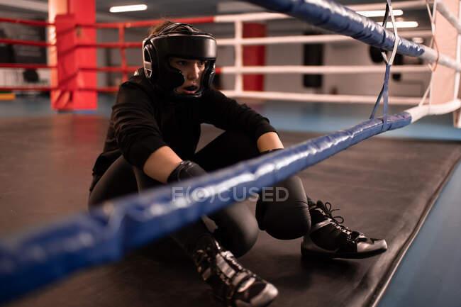 Erschöpfte Frau in Schutzkleidung und Sportbekleidung sitzt nach Boxkampf in moderner Turnhalle auf dem Boden und ruht sich aus — Stockfoto