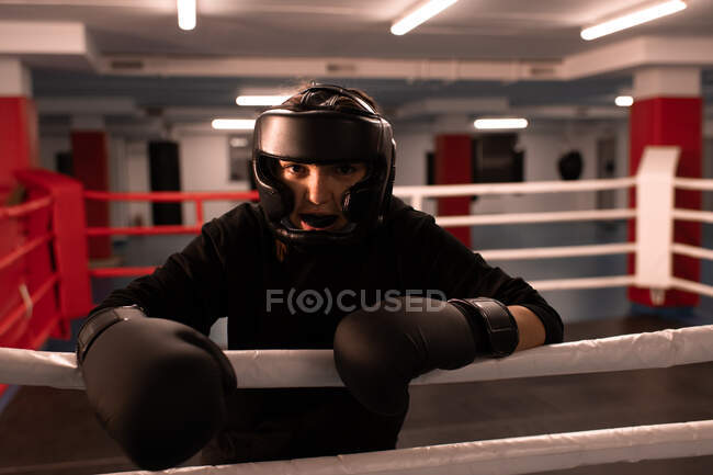 Positive kraftvolle Frau mit Schutzhelm und Handschuhen, die in die Kamera blickt und mit Mundschutz zwischen den Lippen lächelt, während sie sich auf den Boxring stützt und sich auf den Kampf vorbereitet — Stockfoto