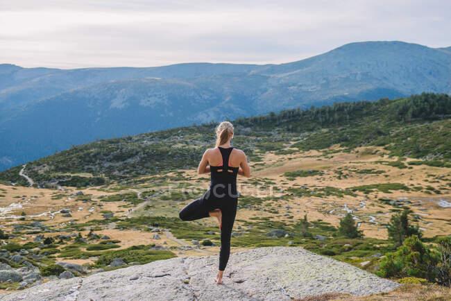 Femme faisant des poses de yoga dans la nature montagne paix — Photo de stock