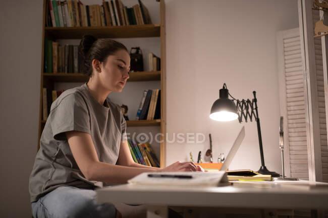 Studentessa intelligente che scrive su netbook mentre studia online da casa — Foto stock