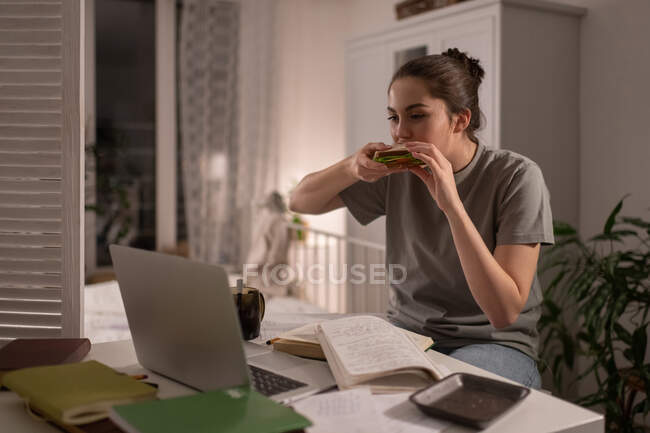 Student sitting and eating delicious sandwich while watching online video lesson — Stock Photo