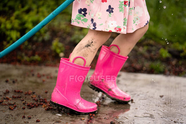 Menina em botas de borracha rosa no fundo da natureza — Fotografia de Stock