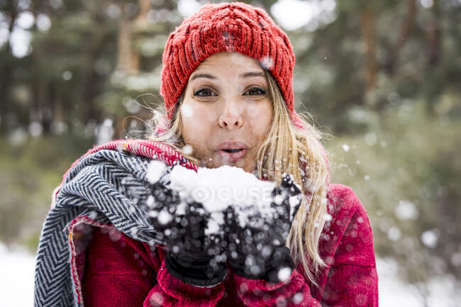 Portrait of happy young woman playing with snow in winter, blowing snowflakes to camera, copy space — Stock Photo